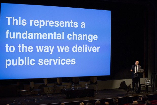 "Mike Bracken on stage at Sprint 15, in front of a large slide saying ""This represents a fundamental change to the way we deliver public services"""