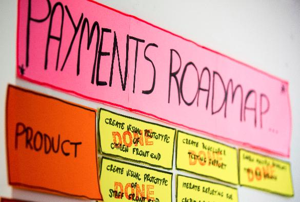 "Pay team's wall with sign saying ""Payments roadmap"""