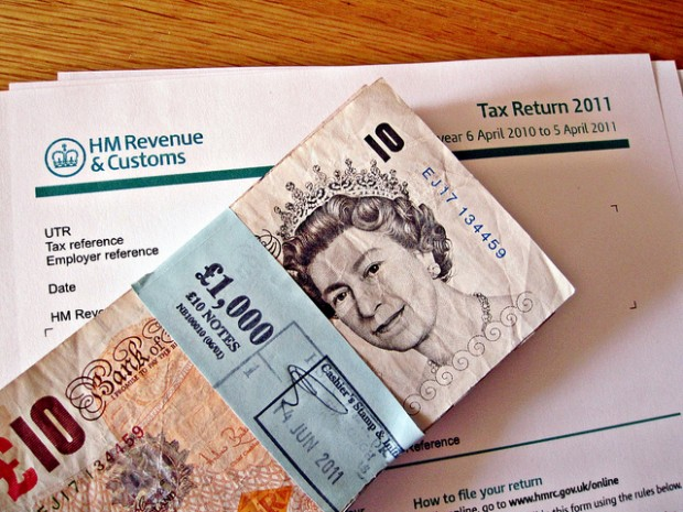 Photo of £1000 cash on top of a 2011 HMRC tax return form