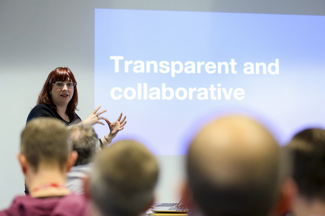 "Photo of a woman giving a talk in front of an audience. Slide on the screen reads ""Transparent and collaborative"". Audience look engaged, and speaker is gesticulating."