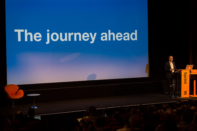 "The journey ahead: Matt Hancock MP on stage with a screen reading ""the journey ahead"" . Photo taken at Sprint 16 GDS event"