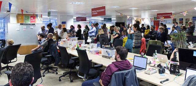 Photo of GDS team listening to an impromptu talk in the Aviation House offices. Bunting, macbooks, signage.