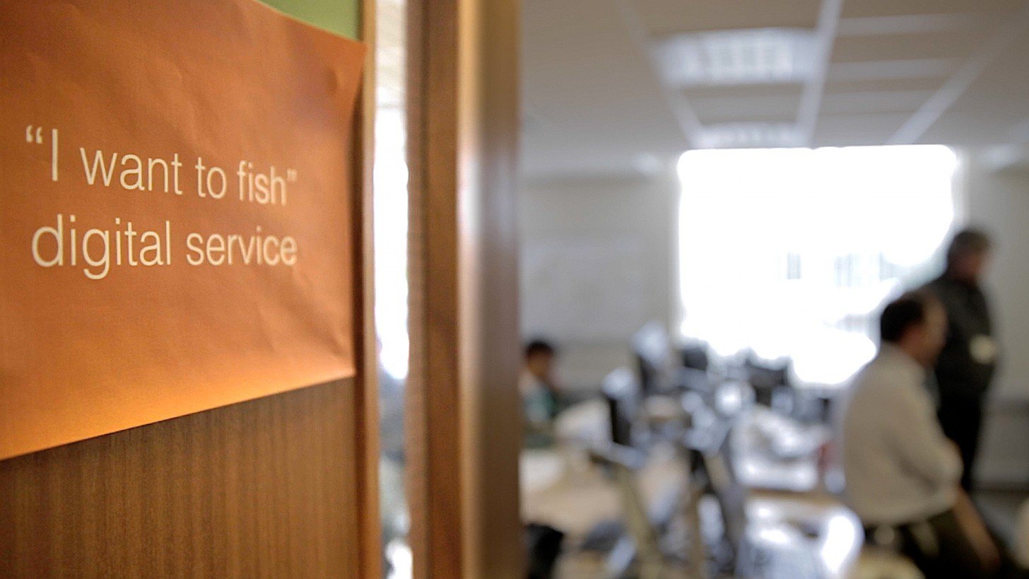 "Poster on a door - ""I want to fish: digital service"" - blurred office scene in background"