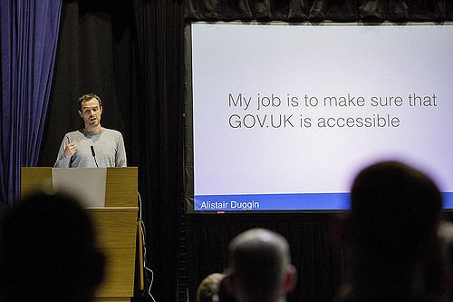 "Photo of Alistair Duggin speaking at a GDS all staff event - slide reads ""My job is to make sure GOV.UK is accessible"""