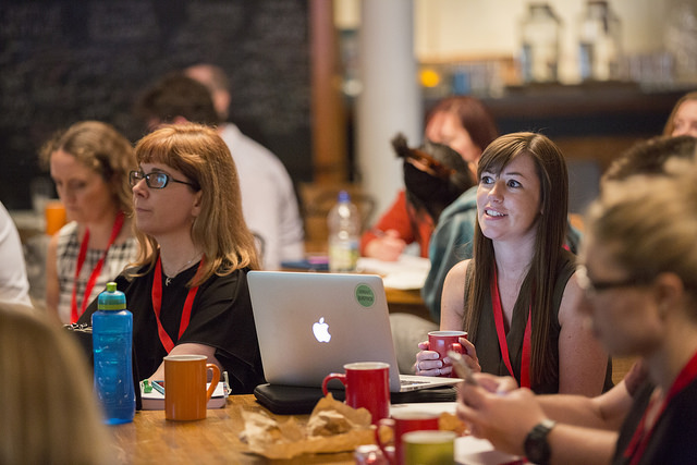 Photo from #GovBlogCamp - audience members sat around tables intently watching the action onstage. Warm, relaxed atmosphere, with macbooks and coffee cups on the tables.