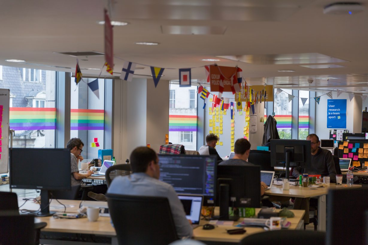 Photo of GDS offices featuring staff working at desks and the rainbow wrap stickers across the windows in the background