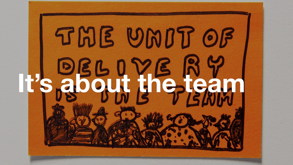 Post-it note showing a Paul Downey illustration of people with the caption 'The unit of delivery is the team' - with 'It's about the team' superimposed over the top