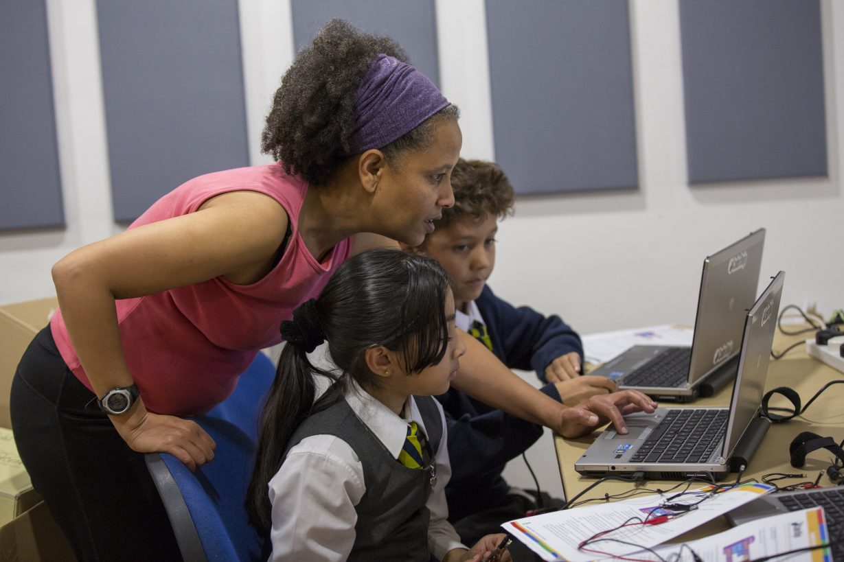 2 children being coached by an adult woman at a computer at Dragon Hall