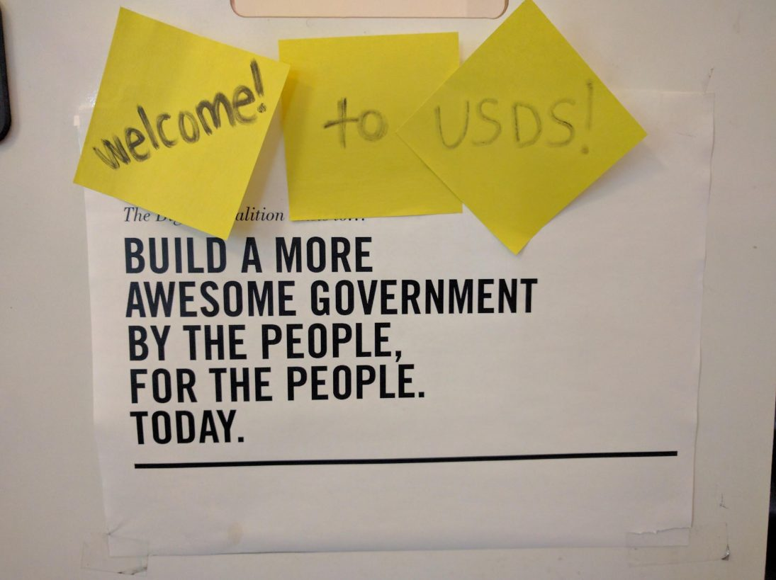 A sign that says 'Build a more awesome government by the people, for the people. Today.' The sign has sticky notes on it that say 'Welcome! to USDS!'