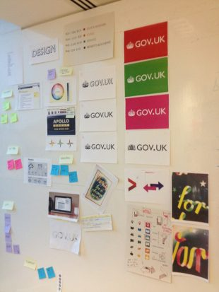 Large wall covered in various different designs of the GOV.UK logo and how that would work on a variety of backgrounds. The wall has a large sign saying Design at the top