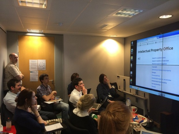 Photograph of 9 team members in the observation room at the new GDS user research lab. They are all looking at a large screen that shows a user on the Intellectual Property Office page of GOV.UK.