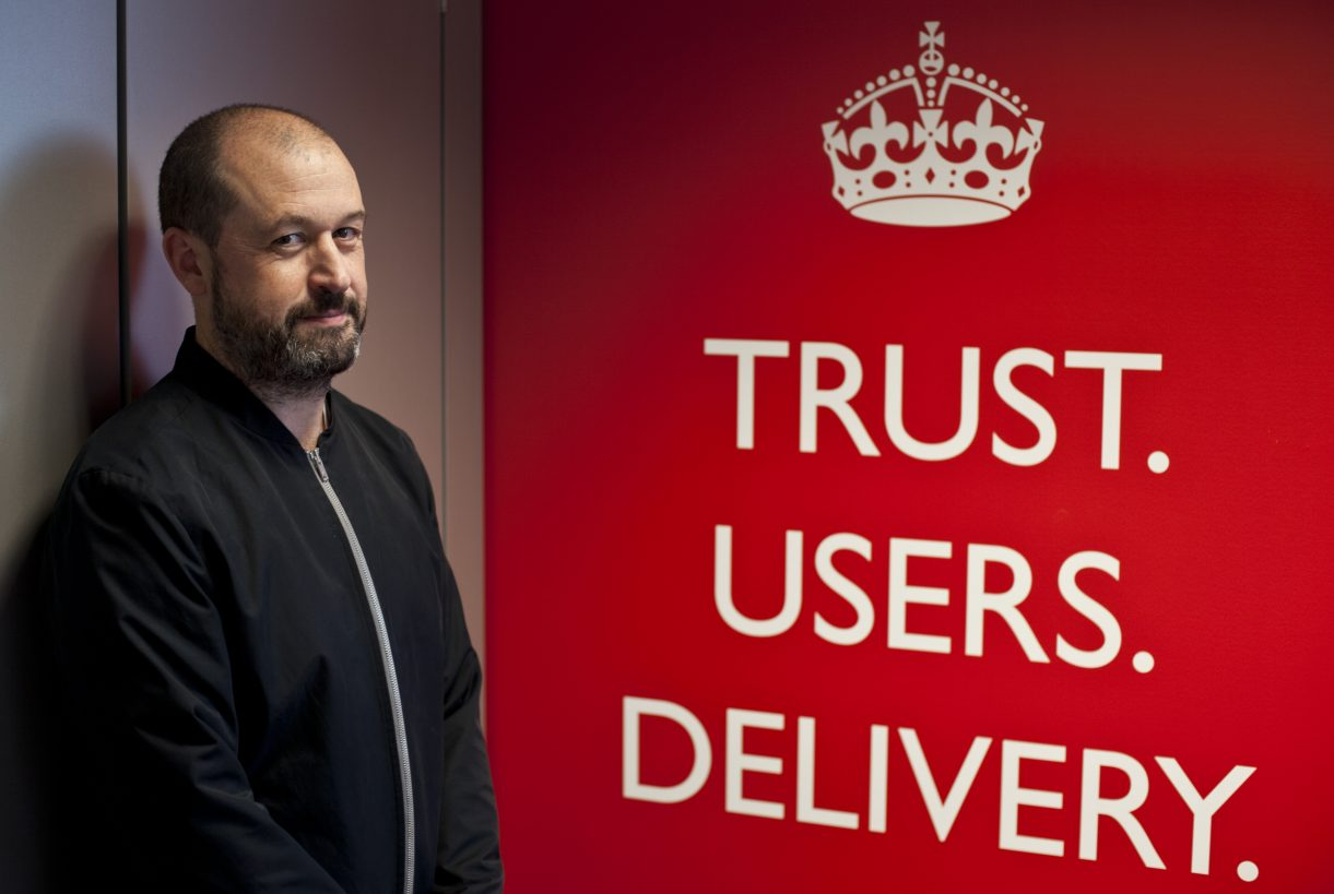 Mike Bracken standing beside a large red poster bearing the crown logo and the words 'Trust. Users. Delivery.'