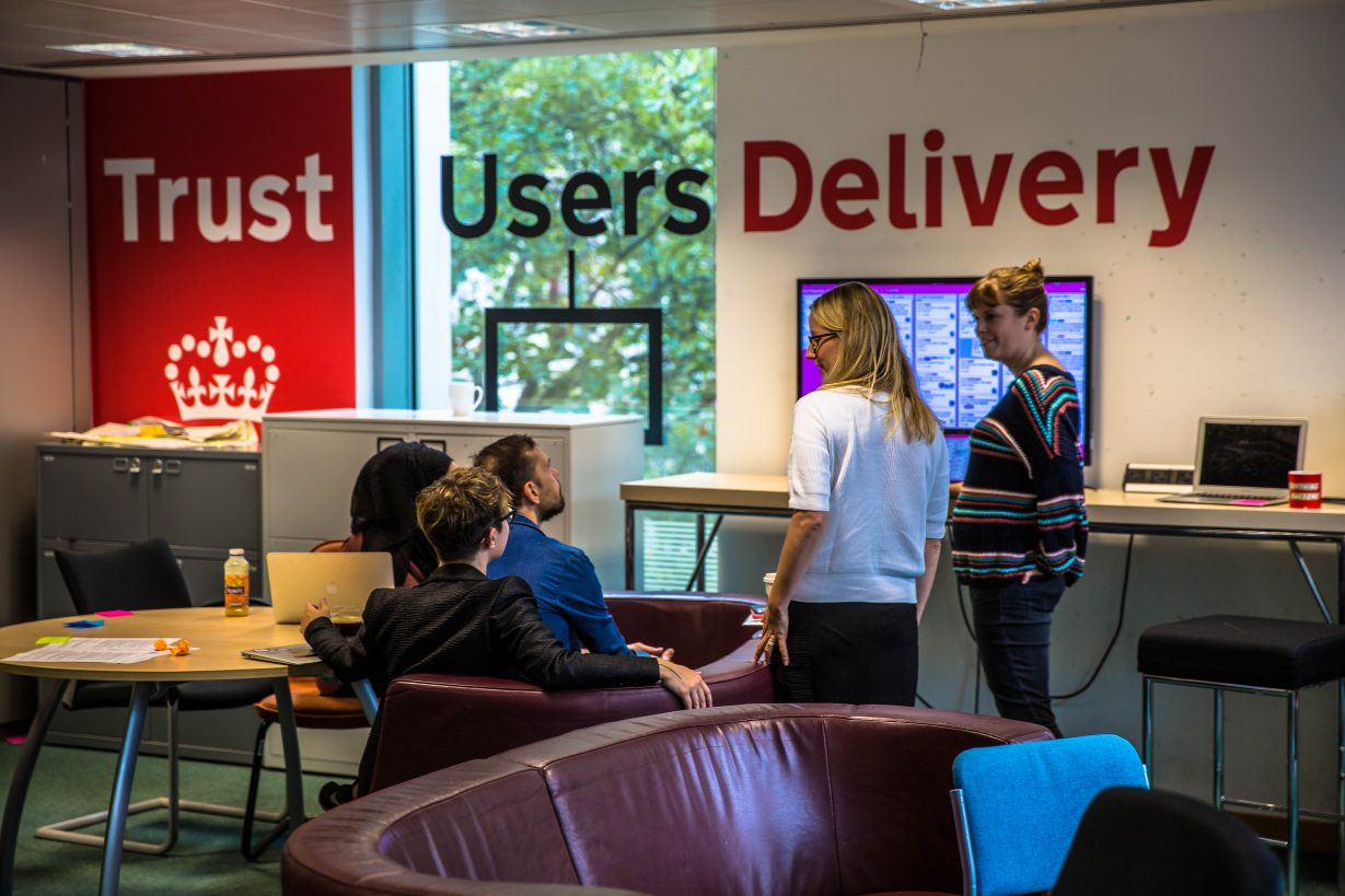 GDS staff in front of the Trust, users, delivery wall sign