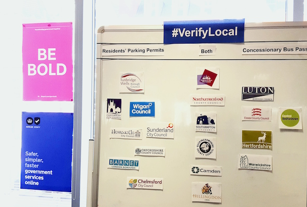 Wall showing a list of local authorities signed up for #VerifyLocal project, including Wigan Council, Chelmsford City Council, Camden Council, Warwickshire County Council, Sunderland City Council and others.