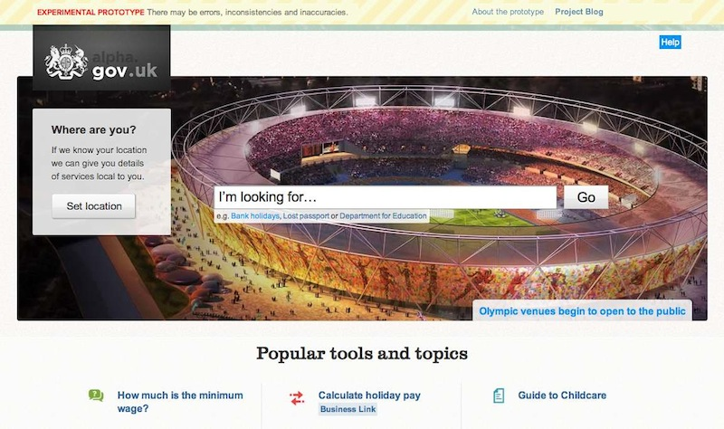 The GOV.UK alpha home page on launch day. There is a large header image of the Olympic stadium with the GOV.UK search bar over the top of it.