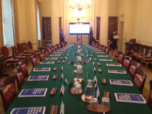 Photo of the Cabinet Room at Number 10, there is a long green table set out with paper briefing packs, iPads on stands, and a big TV screen at the end of the table ready for a meeting with GDS.