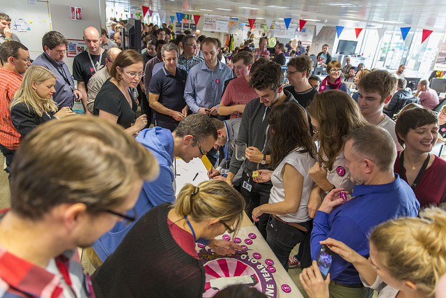 Over 100 members of the GDS team crowd around a table to get cake and pin badges to celebrate the 1st year of GOV.UK