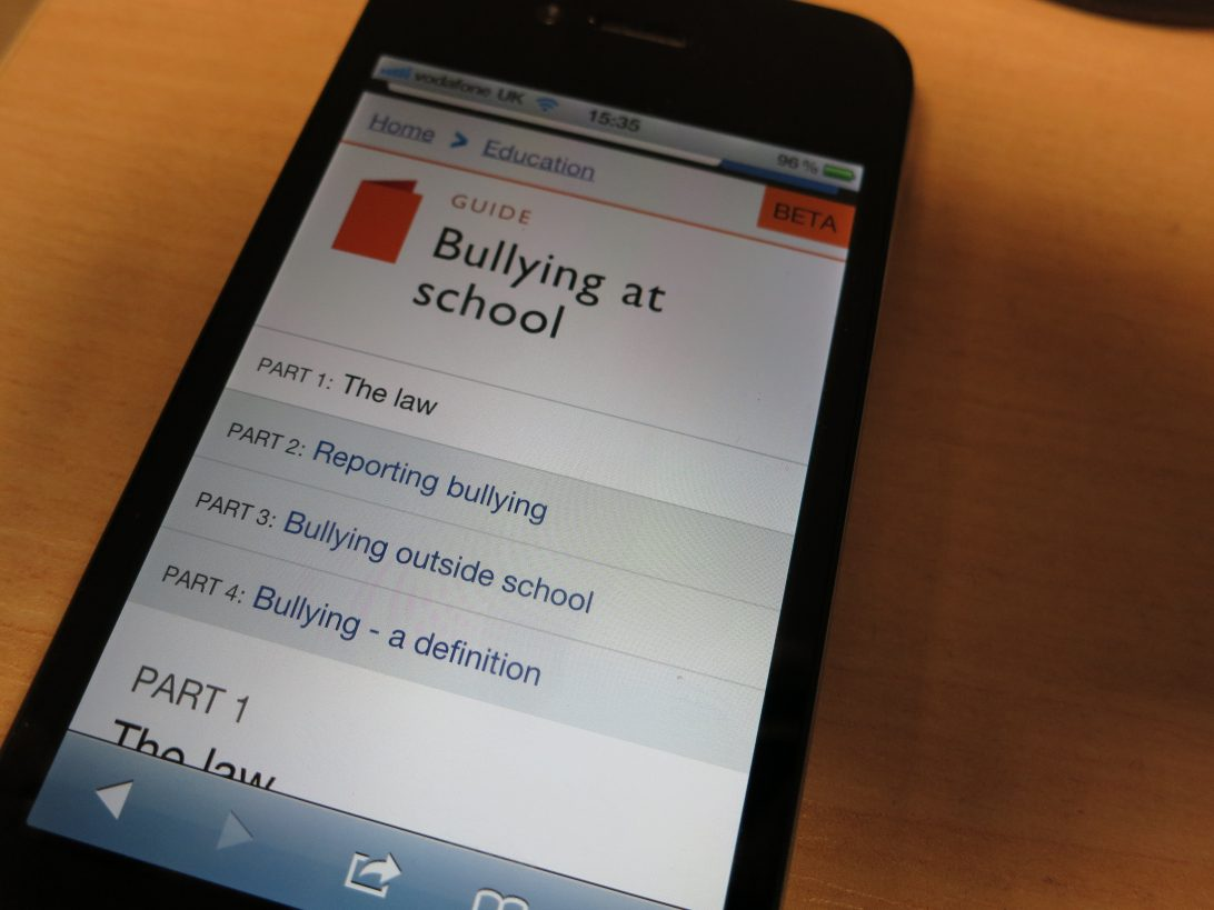 A photo of an iPhone 4 displaying the 'Bullying at school' guide on the GOV.UK beta