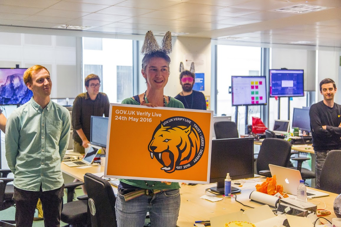 "Photo of the the GOV.UK Verify team celebrating going live. Team leader Janet Hughes is shown holding a sign saying ""GOV.UK Verify Live. 24 May 2016""."