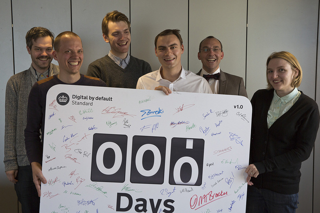 Photo of members of the team working on the Service Manual on day 0. They're all smiling and holding a large signed board that says 000 Days.