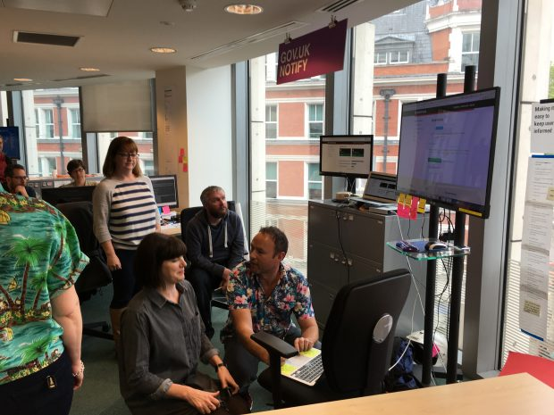Photo showing the GOV.UK Notify team gathered around a computer and a large external monitor to send the first messages via the service.