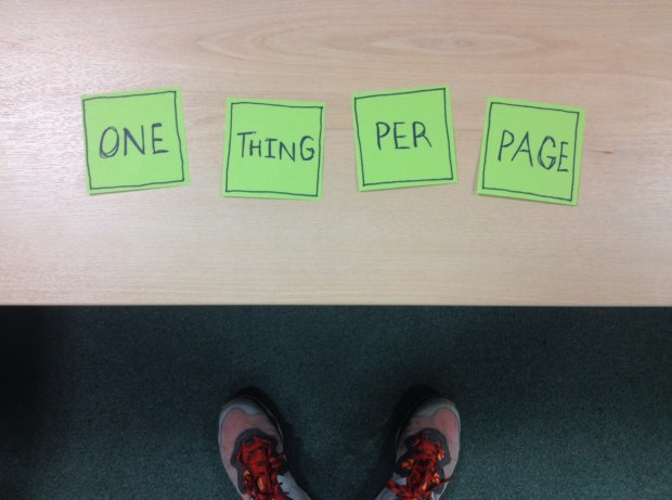 "Sticky notes on a desk saying ""One thing per page"""