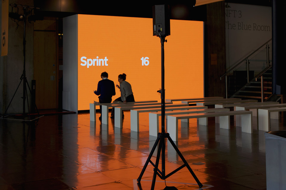 """Photo of Sprint 16 venue, taken shortly before the doors opened. Two members of the production team sit in front of a large screen showing the """"Sprint 16"""" branding on a bright orange background."""