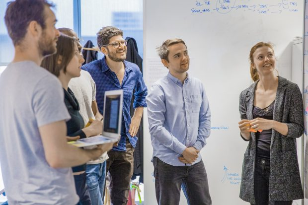GOV.UK team members standing and looking at a whiteboard