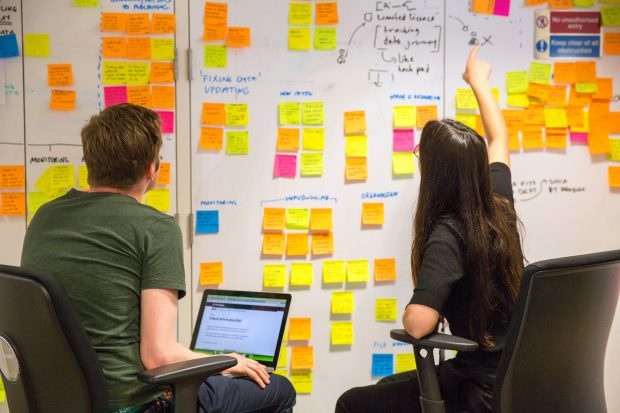 designers in front of a board with post-it notes