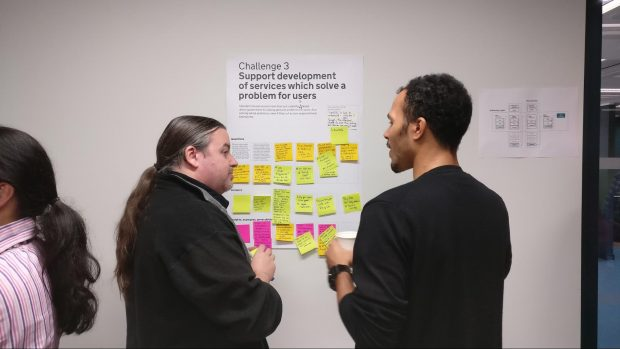 two people standing in front of a poster with post-it notes on it and talking