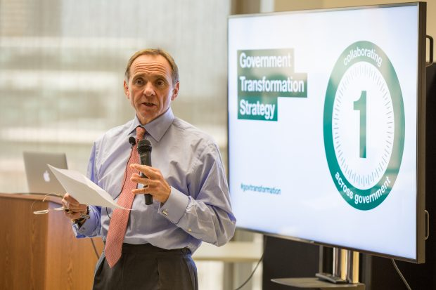 John Manzoni in front of a screen that says 'Government Transformation Strategy', speaking to GDS staff