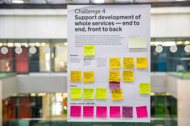a poster from one of the workshop with post-it notes with ideas, the only legible piece of text on it is 'Challenge 4: Support development of whole services - end to end, front to back'