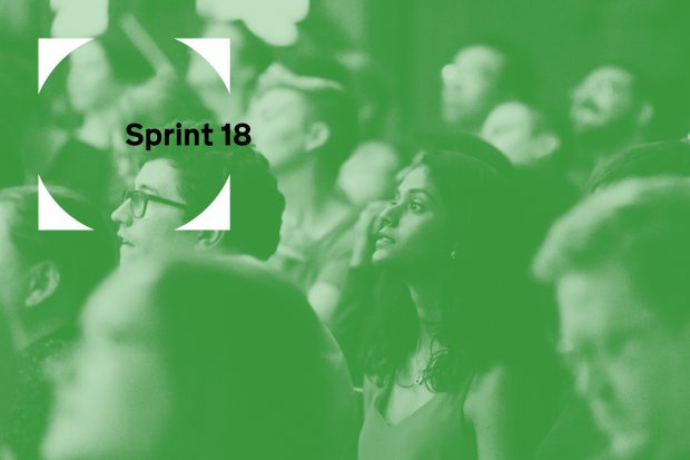 a green image with the Sprint 18 logo and people listening to a talk in the background