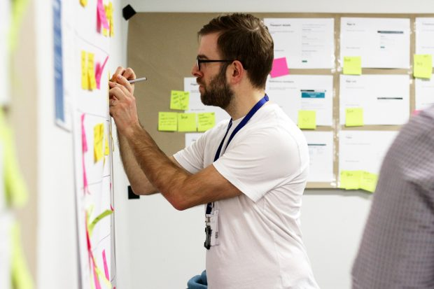 Member of staff at a design systems meet up, writing on a post-it note on a wall