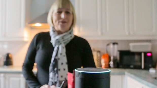 Woman in her kitchen using a voice activated gadget