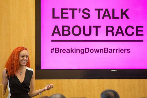 An image of GDS's Tia Priest at the event standing in front of a screen saying: Let's Talk About Race