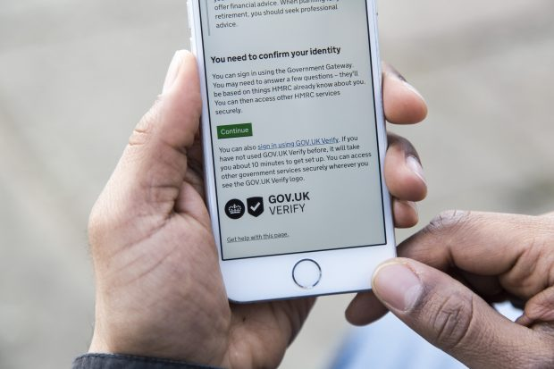 A mobile phone using an HMRC service which requires the user to confirm their identity. The text reads: You can also sign in using GOV.UK Verify. If you have not used GOV.UK Verify before, it will take about 10 minutes to get set up. You can access other government services securely wherever you see the GOV.UK Verify logo.""