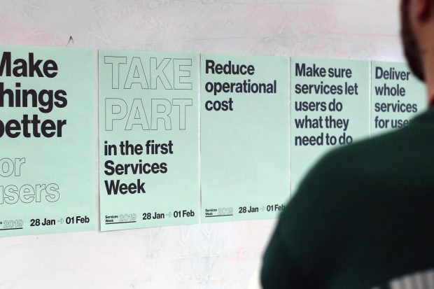 "A wall with Service Week posters on it. One says ""Make things better for users', a second says ""Take part in the first Services Week"", a third says ""Reduce operational cost"", a fourth says ""Make sure services let users do what they need to do"" and a fifth says ""Deliver whole services for users"""