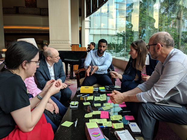 6 people sitting around a table and talking, the table is covered with post-it notes