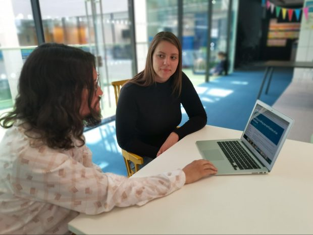 two people sitting at a table, one of them looking at a laptop, the other one facing the camera
