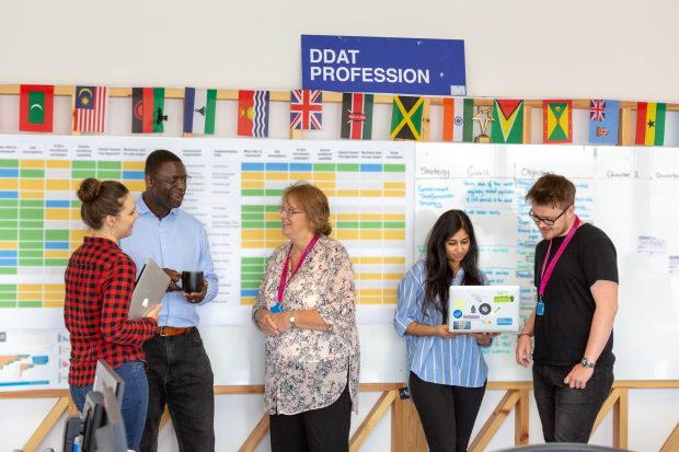 5 people standing in front of a board with a roadmap on it and a sign saying 'DDaT Profession'