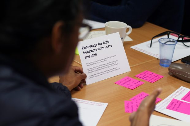 the back of a person sitting at a desk with some post-it notes on it, and a card that says 'encourage the right behaviours from users and staff'