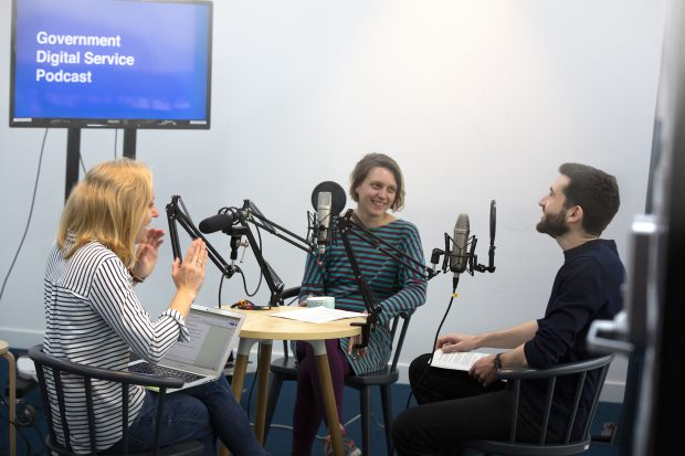 3 people sitting around a table in a recording studio, speaking to microphones. There is a screen behind them that says 'Government Digital Service Podcast'
