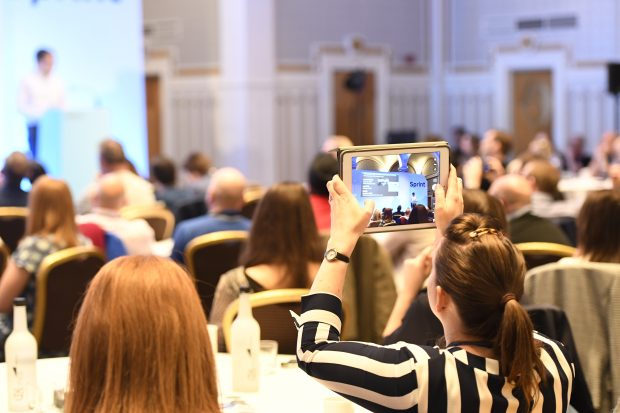 An audience facing away from the camera, one person in the foreground holding up an ipad and taking a picture of the presenter, who is visible in the background but blurry