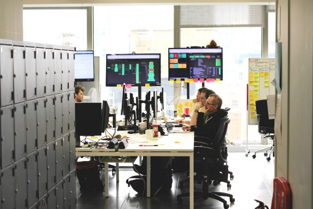 Members of the GOV.UK Verify team at work, sitting at desks and looking at their computer screens