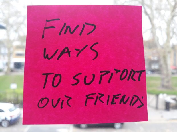 A post-it note on a window, saying 'find ways to support our friends'
