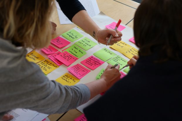 group of people writing on post-it notes, which are attached to a sheet of paper on a table