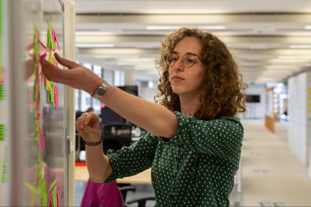 Anna putting post-it notes on a whiteboard
