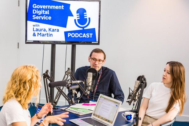 the interviewer and 2 interviewees in the recording studio, the screen behind the says 'Government Digital Service podcast, with Laura, Kara and Martin'