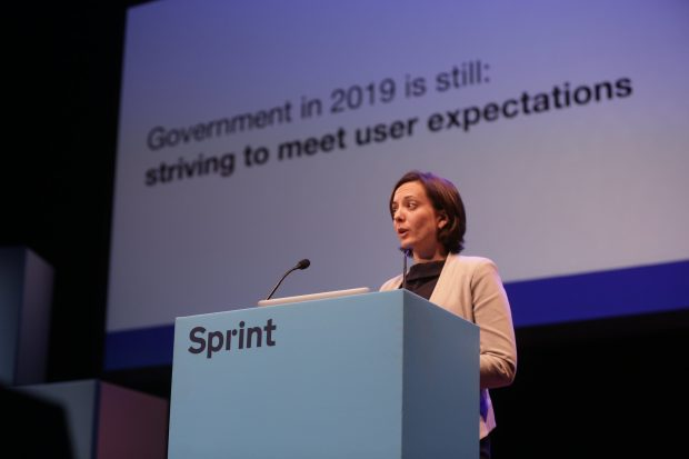 Jen Allum on the stage, with a screen in the background reading 'Government in 2019 is still striving to meet user expectations'